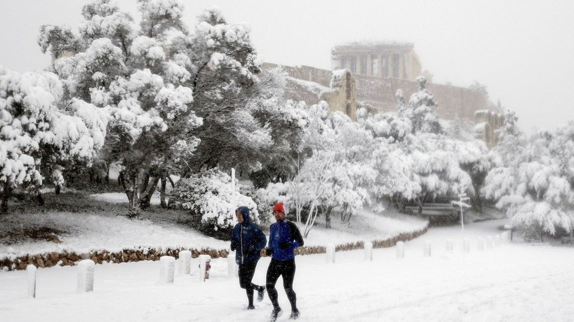 Two men jog as the Parthenon temple is seen atop the Acropolis hill archaeological site during a heavy snowfall in Athens, Greece, on February 16, 2021. (Reuters)