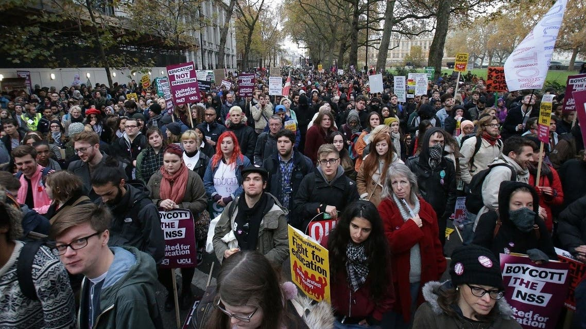 Demonstrators hold up placards at a protest march through central London on November 19, 2016 called by the National Union of Students and University College Union to demand free, quality further and higher education, accessible to all. (Daniel Leal-Olivas/AFP)