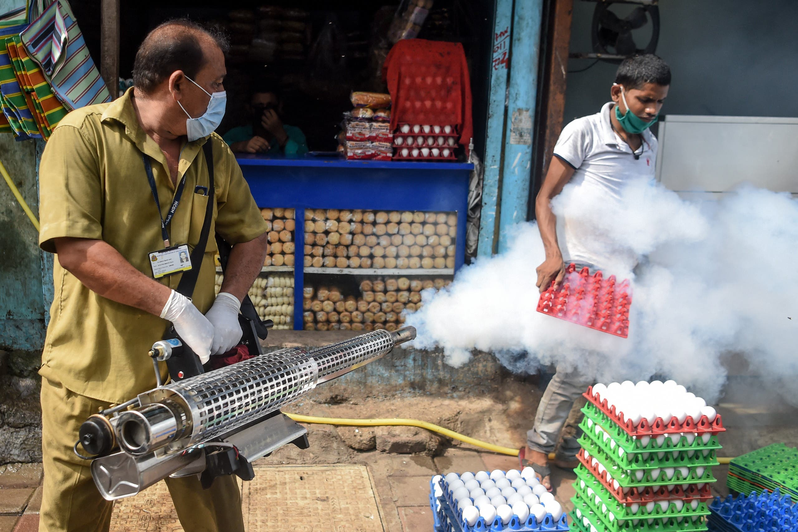A civic worker fumigates a slum area as a preventive measure against malaria and dengue ahead of monsoon in Mumbai on June 12, 2020. (File photo: AFP)