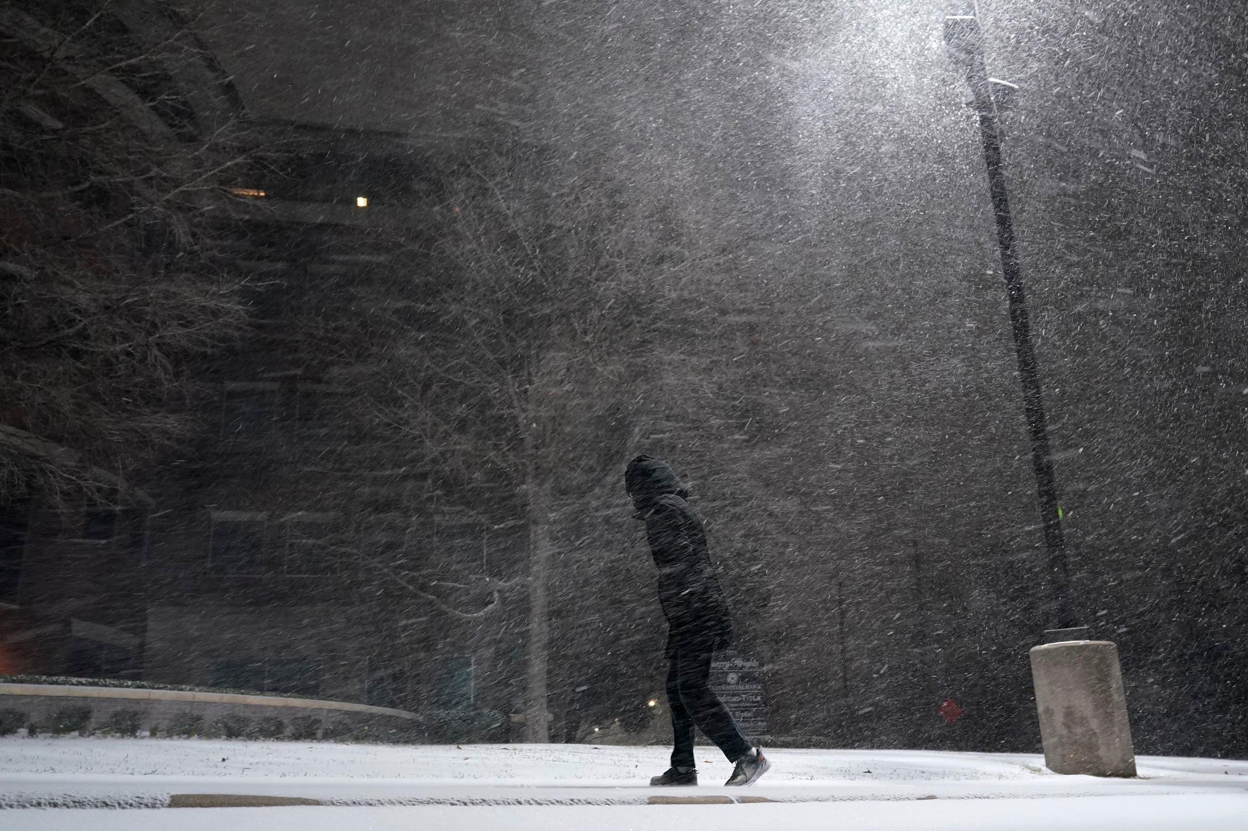 A woman walks through falling snow in San Antonio, Sunday, Feb. 14, 2021. (AP)