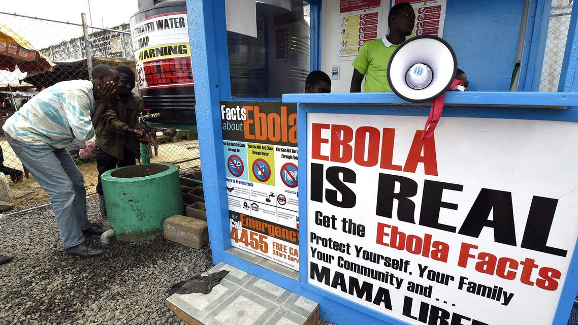 Liberians wash their hands next to an Ebola information and sanitation station, raising awareness about the virus in Monrovia, September 30, 2014. (File photo: AFP)