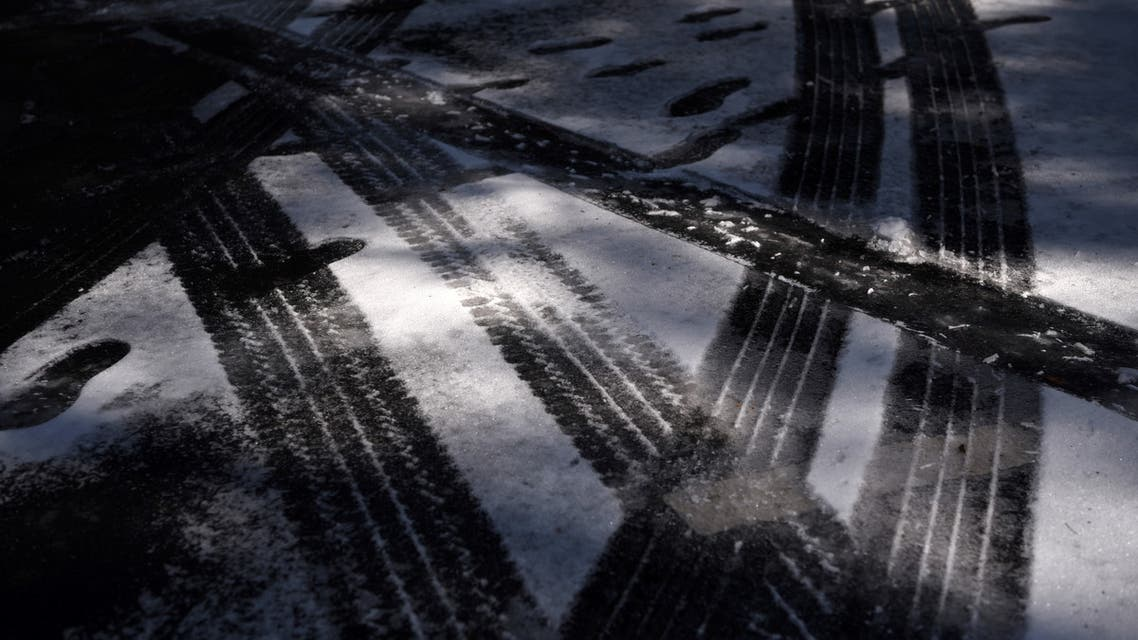 Tire tracks and footsteps are seen in the snow as the state of Texas experiences widespread power outages and record-breaking temperatures in Houston, US, February 16, 2021. (Reuters)