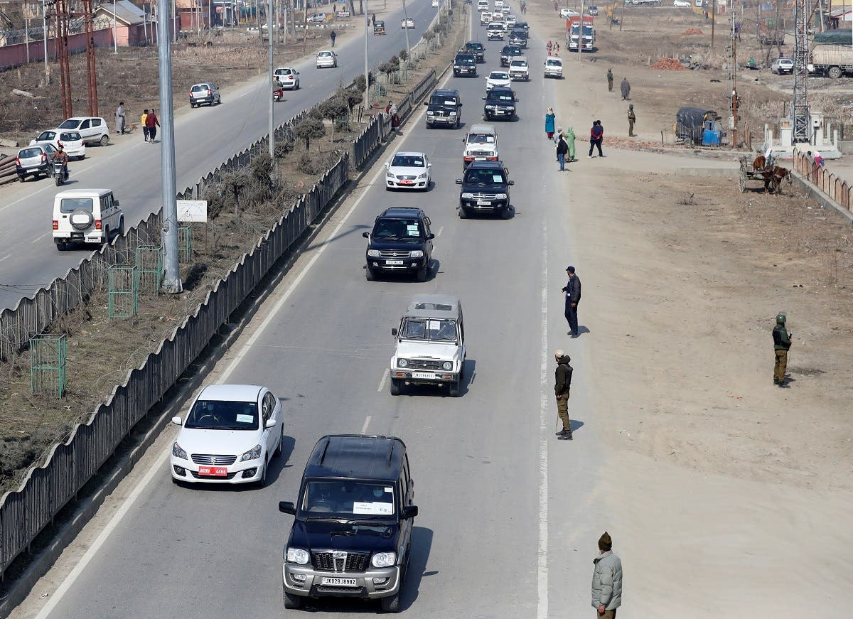 Indian policemen stand guard as a convoy carrying foreign diplomats moves on a road in Srinagar, on February 17, 2021. (Reuters)