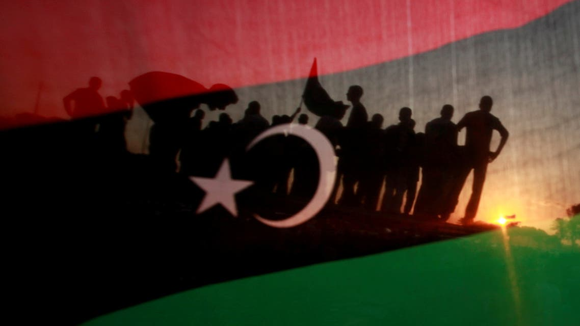 FILE PHOTO: Libyans are seen through a Kingdom of Libya flag during a celebration rally in front of the residence of Muammar Gaddafi at the Bab al-Aziziyah complex in Tripoli September 13, 2011. REUTERS/Suhaib Salem/File Photo SEARCH 10TH ANNIVERSARY OF THE 2011 REVOLUTION IN LIBYA FOR THE PHOTOS.