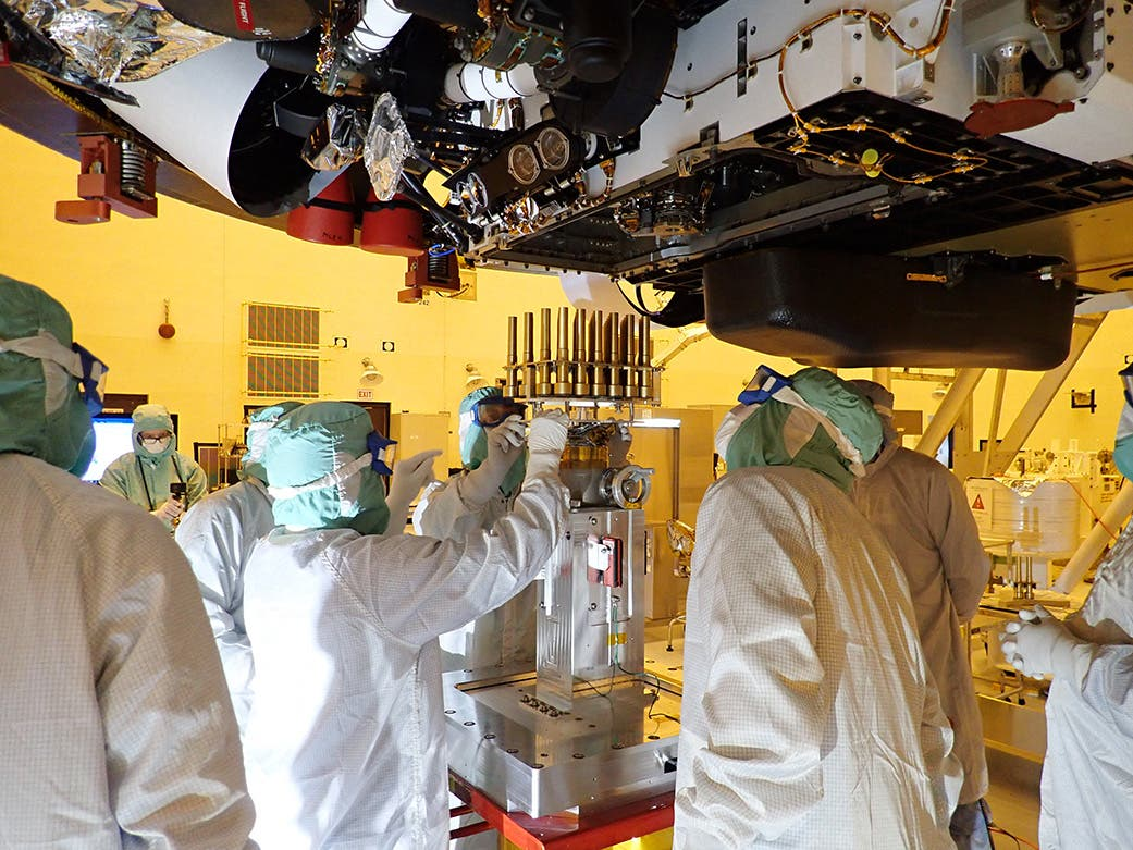 This NASA photo obtained July 20, 2020 shows an image taken on May 20, 2020 at the Kennedy Space Center, Florida as engineers and technicians insert 39 sample tubes into the belly of the Mars rover. NASA's Perseverance rover mission will collect the first samples from another planet for return to Earth. (AFP)
