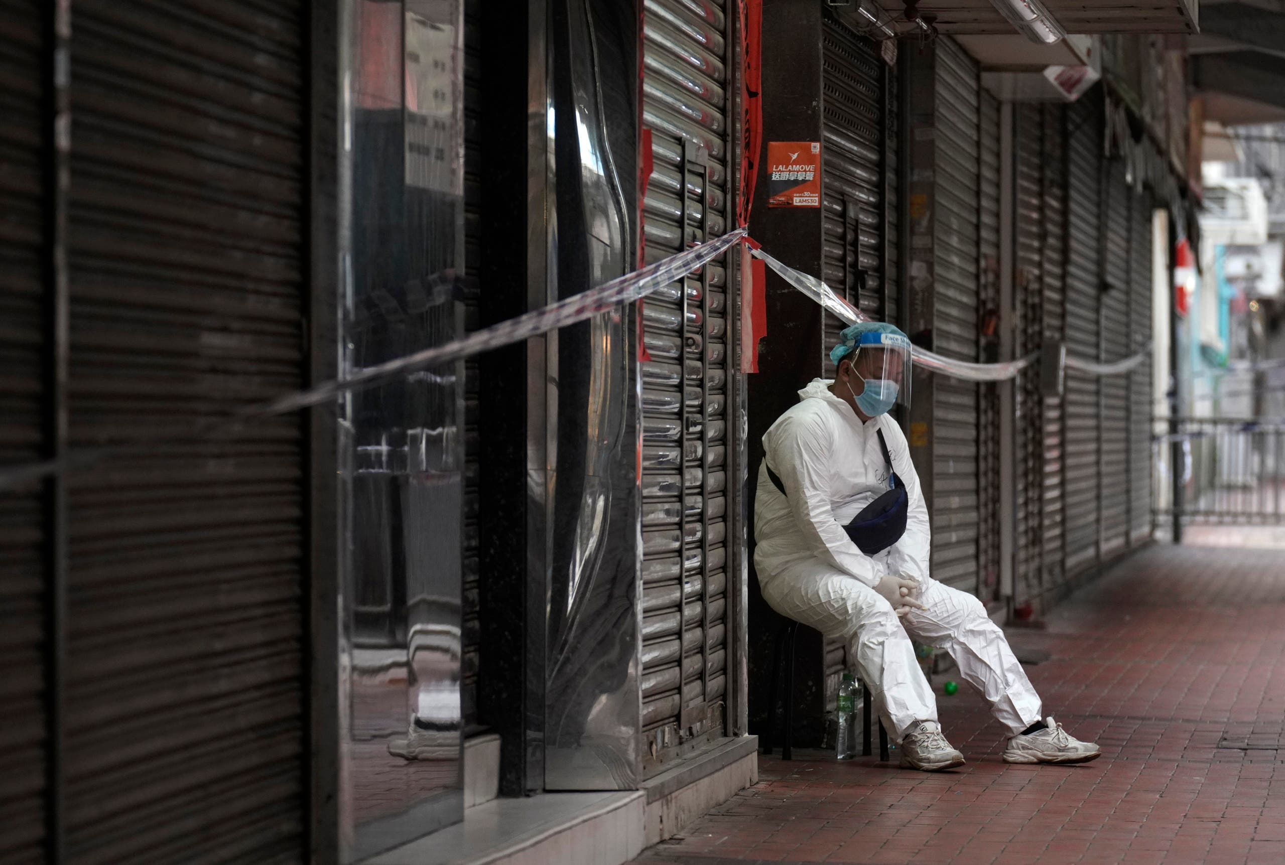 A government worker wearing personal protective equipment guards at the closed area in Jordan district, in Hong Kong, Sunday, Jan. 24, 2021. (AP)