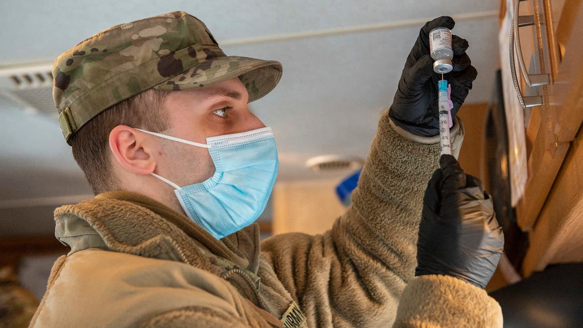 (FILES) In this file photo taken on February 04, 2021, a soldier fills syringes with the Moderna Covid-19 vaccine inside a trailer at a vaccination center in Londonderry, New Hampshire. Pentagon officials said on February 17, 2021, that about one-third of the US military are declining to receive the Covid-19 vaccine, despite significant coronavirus infection levels in the forces. Major General Jeff Taliaferro revealed the high refusal rate in Congressional hearing, as the US Defense Department continues to classify covid vaccines as optional because they have yet to receive full approval from the Federal Drug Administration.
