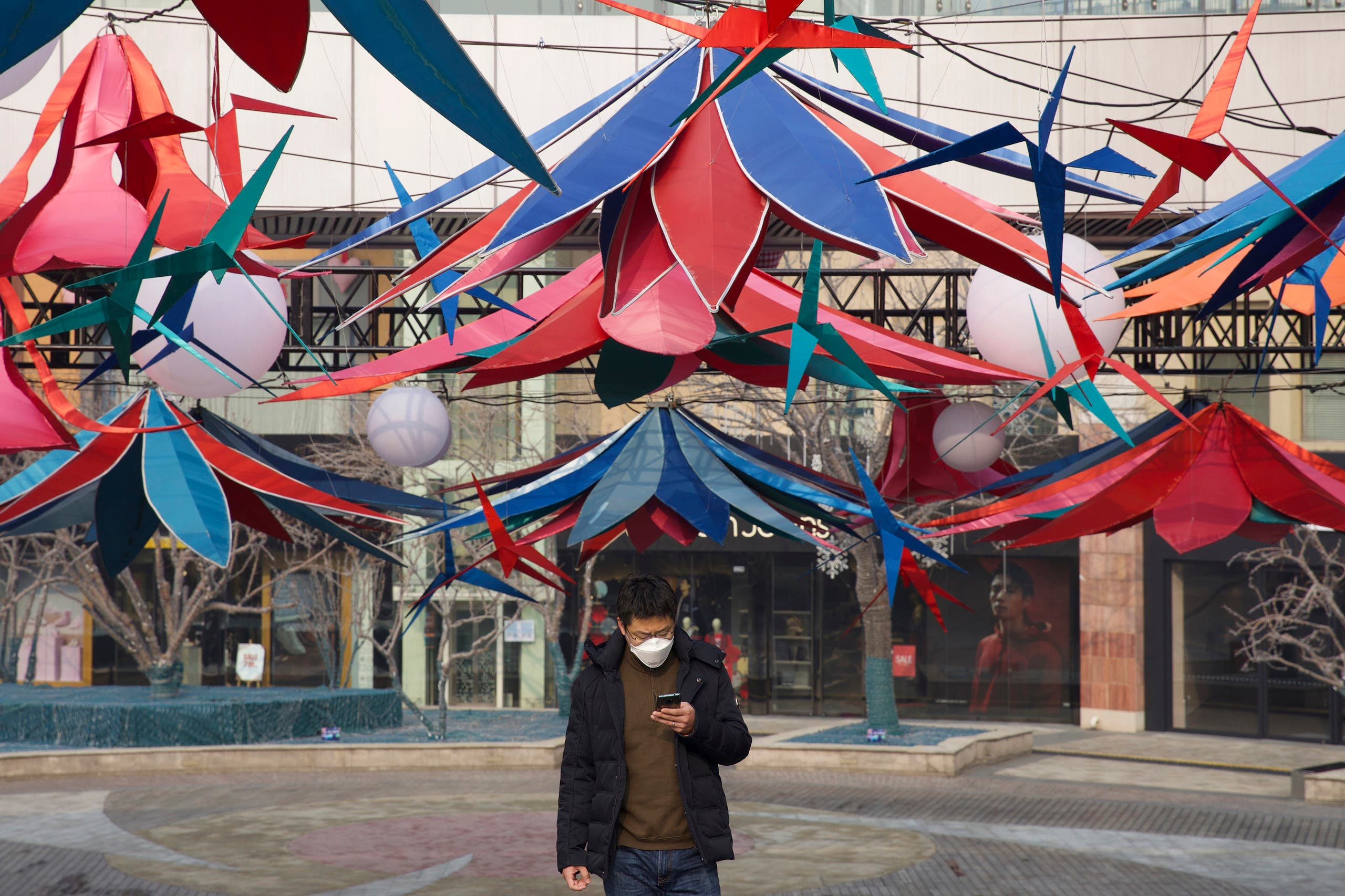 A man uses his phone as he walks through an empty mall district in Beijing, China Wednesday, Feb. 12, 2020. (AP)