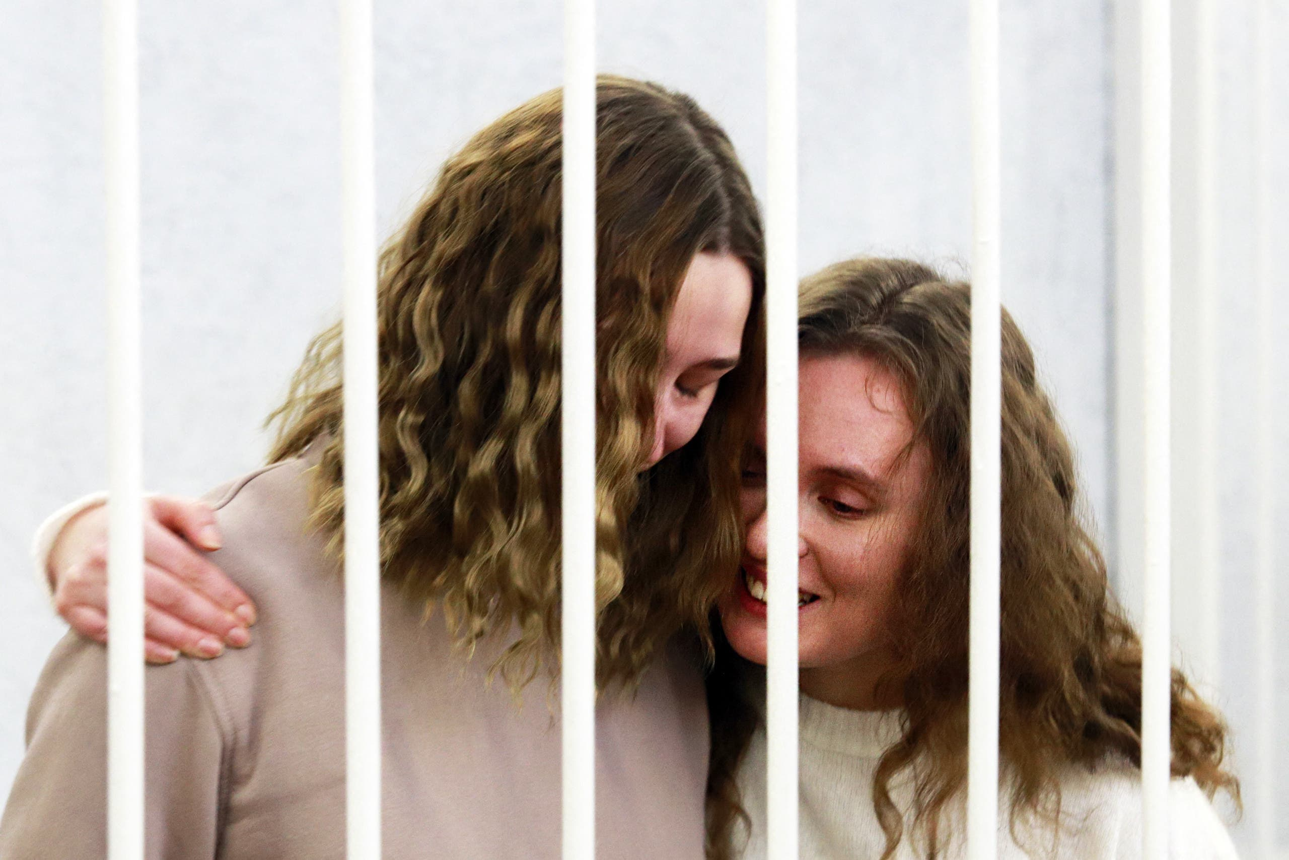 Belsat TV journalists Katerina Bakhvalova (R) and Daria Chultsova (L), who were detained in Nov 2020 while reporting on anti-government protests, embrace each other in a defendants' cage before the start of their trial in Minsk. (File photo: AFP)