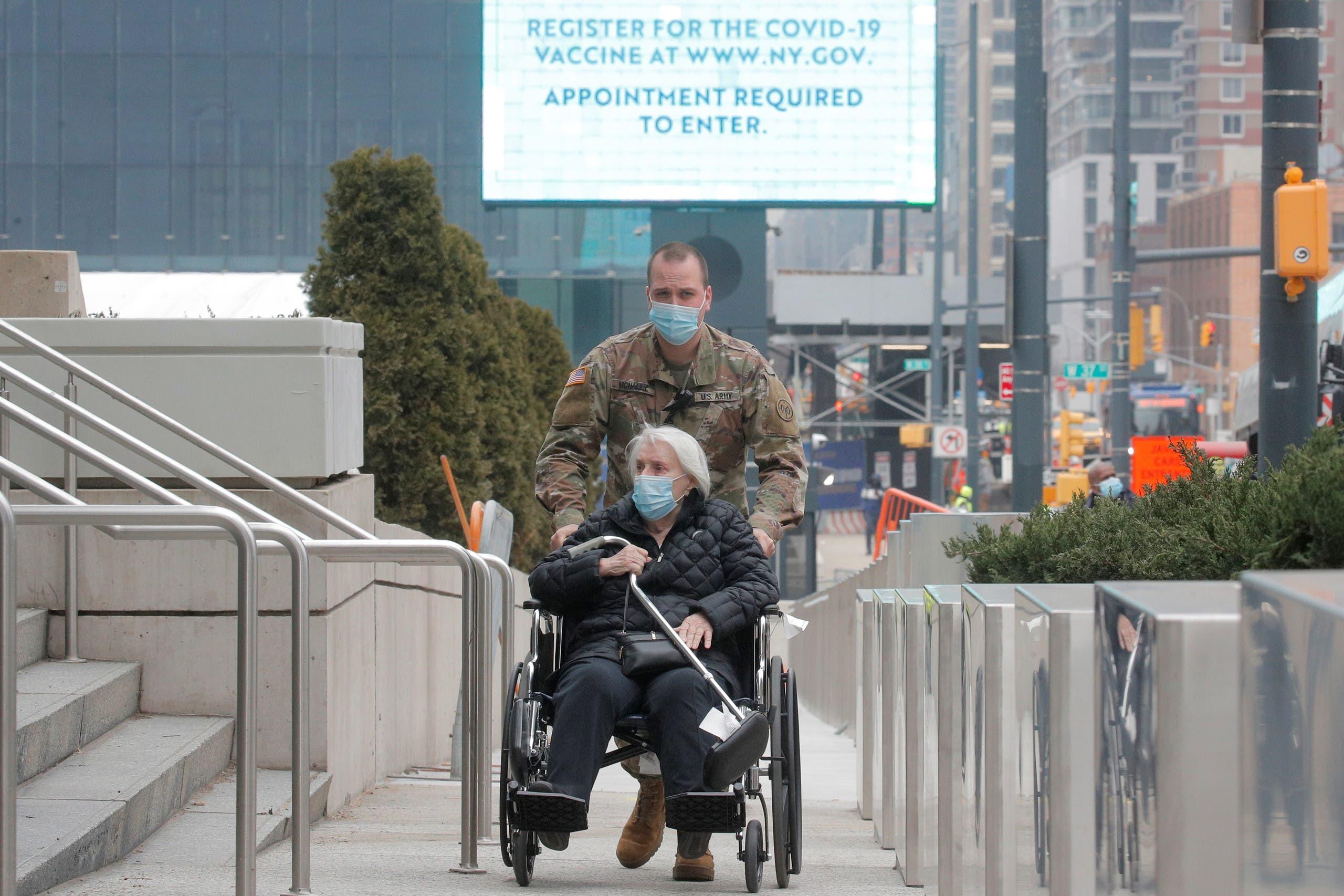 جندي أميركي يوصل سيدة مسنة إلى مركز تطعيم في نيويورك