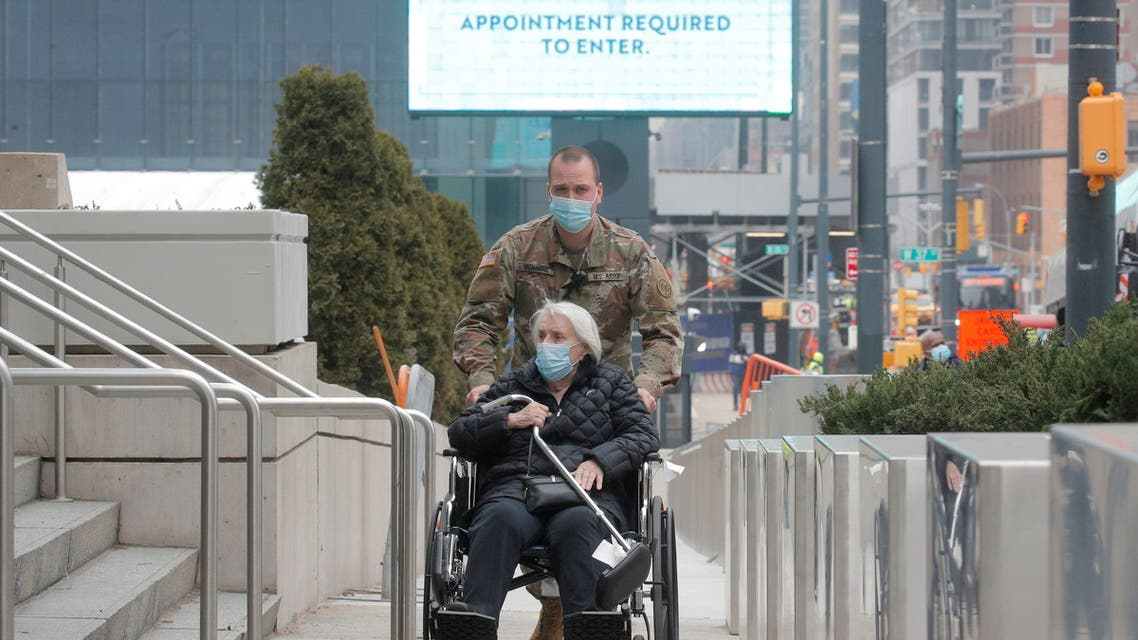A soldier assists an elderly woman as she arrives to receive a dose of the coronavirus disease vaccine at the New York State COVID-19 vaccination site at the Jacob K. Javits Convention Center, in New York City, U.S., January 15, 2021. REUTERS/Brendan McDermid