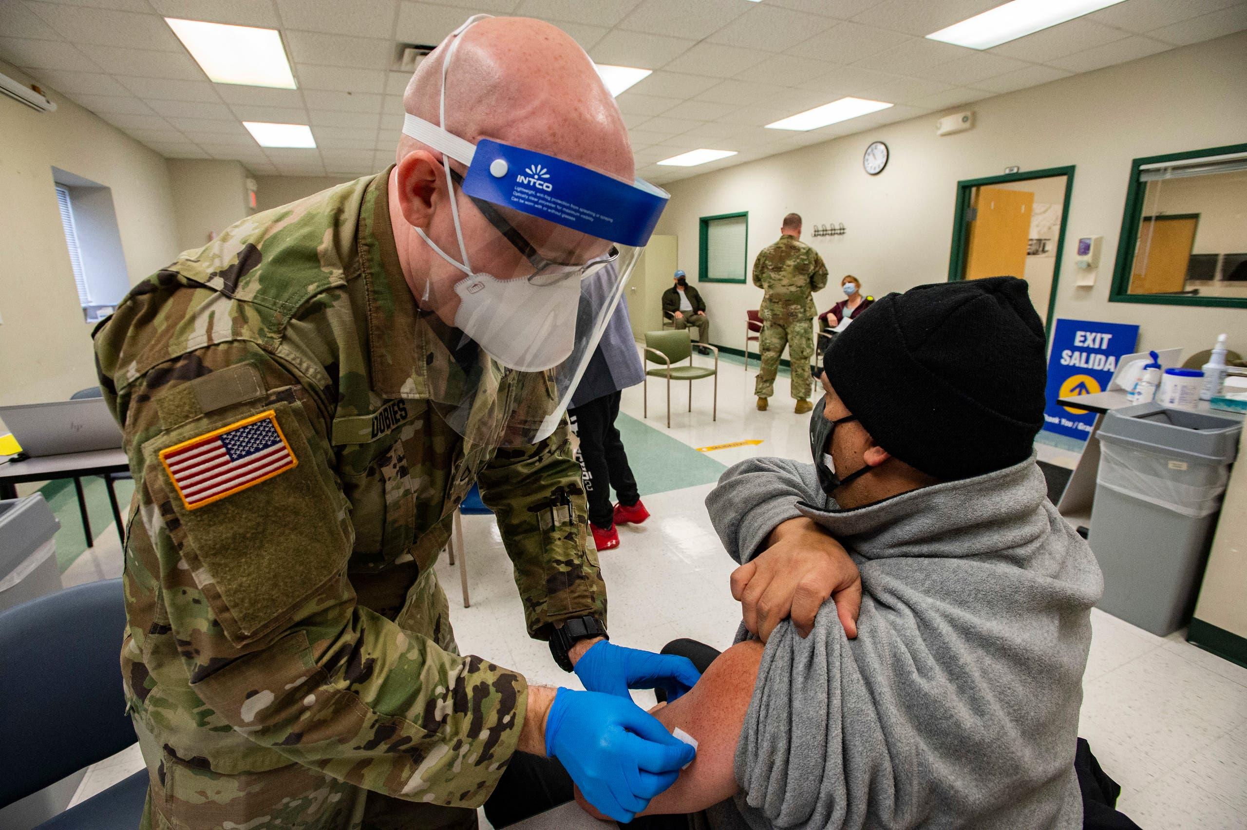 جندي أميركي يعطي جرعة من لقاح كورونا لمسن في مركز تطعيم في ماساشوستس