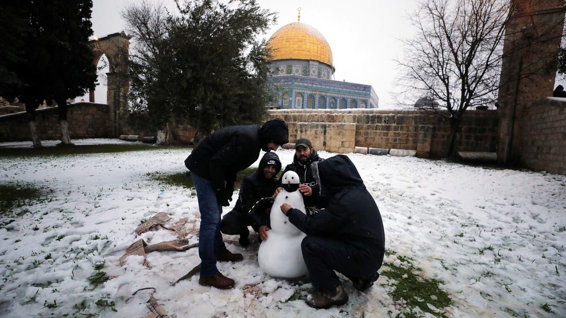 As pessoas tocam no Domo da Rocha no complexo durante uma manhã de neve na Cidade Velha de Jerusalém, 18 de fevereiro de 2021. (Reuters)