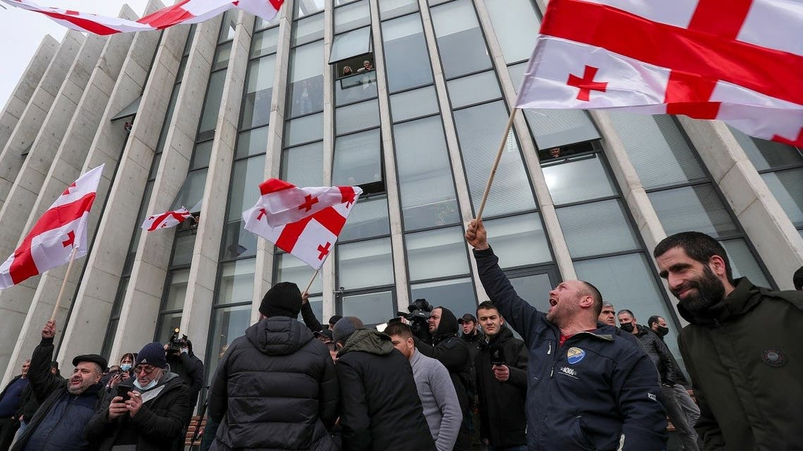 Opposition supporters wave flags following the announcement of Georgian Prime Minister Giorgi Gakharia's resignation outside the headquarters of the United National Movement (UNM) party in Tbilisi, Georgia, on February 18, 2021. (Reuters)