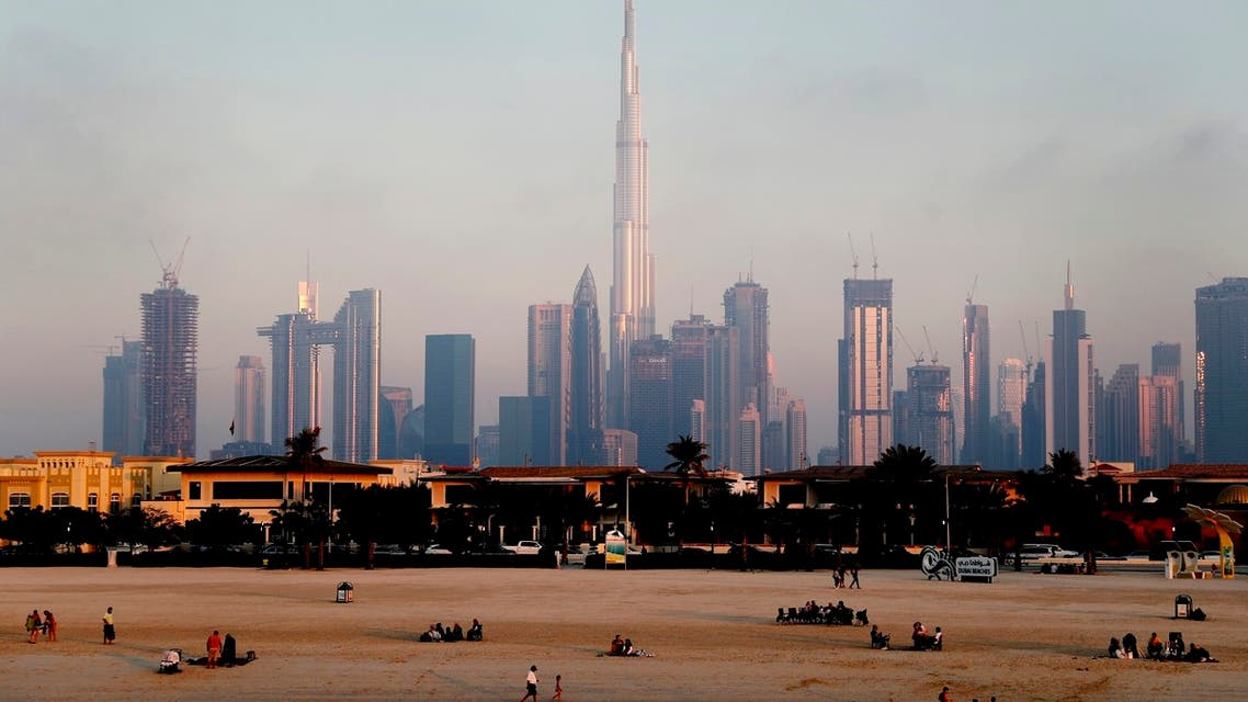 People enjoy the beach in front of the city skyline with the world tallest tower, Burj Khalifa, in Dubai, United Arab Emirates, Friday, Feb. 12, 2021. (AP)