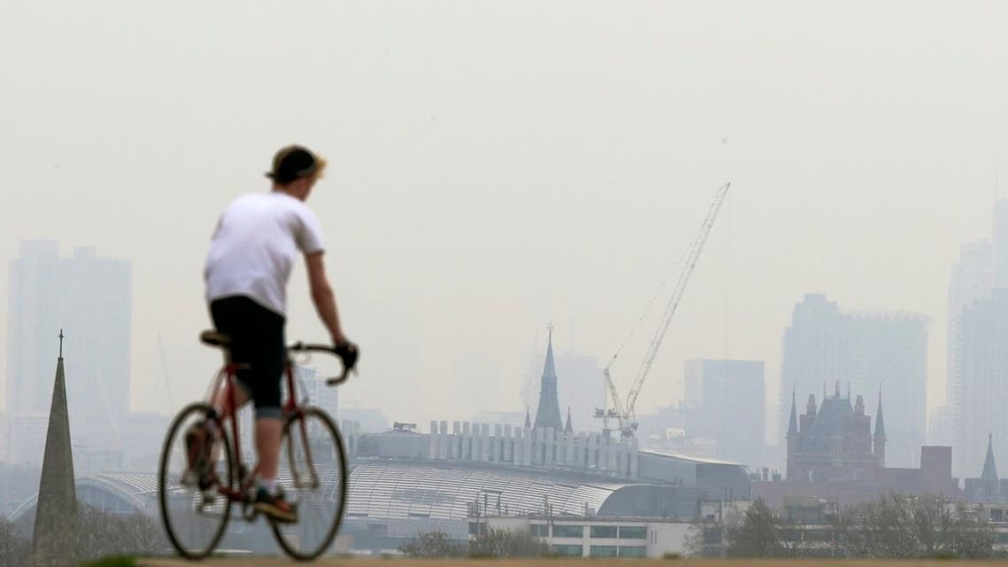 A cyclist rides his bike at the top of Primrose Hill in London on April 3, 2014, as the city below lies shrouded in pollution. A combination of local emissions, light winds and pollution from continental Europe, compounded with dust blown from the Sahara, has prompted health warnings about poor air quality across southern and central England. (AFP)