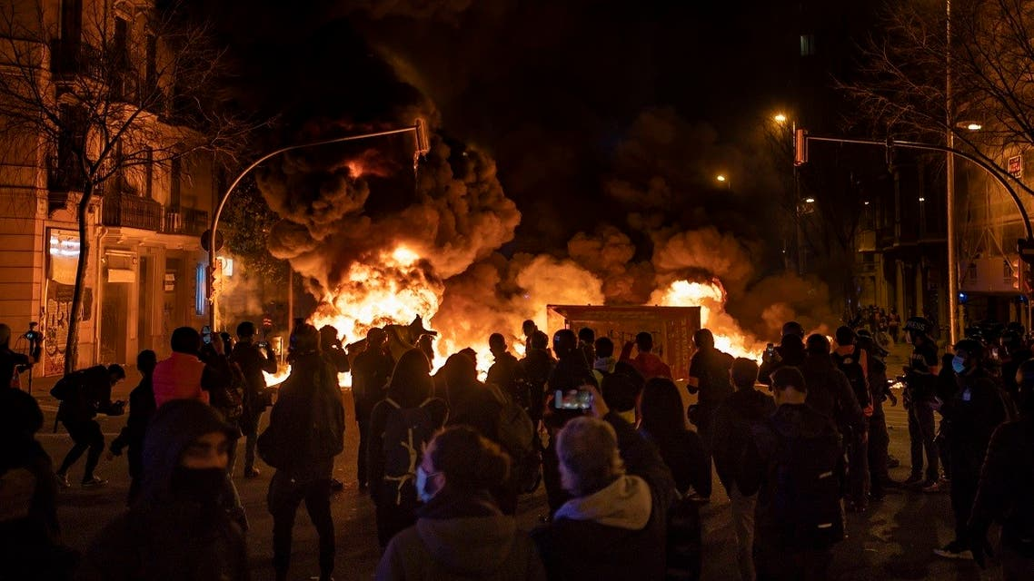 Demonstrators gather near a burning barricade during clashes with police following a protest condemning the arrest of rap singer Pablo Hasél in Barcelona, Spain, on February 18, 2021. (AP)