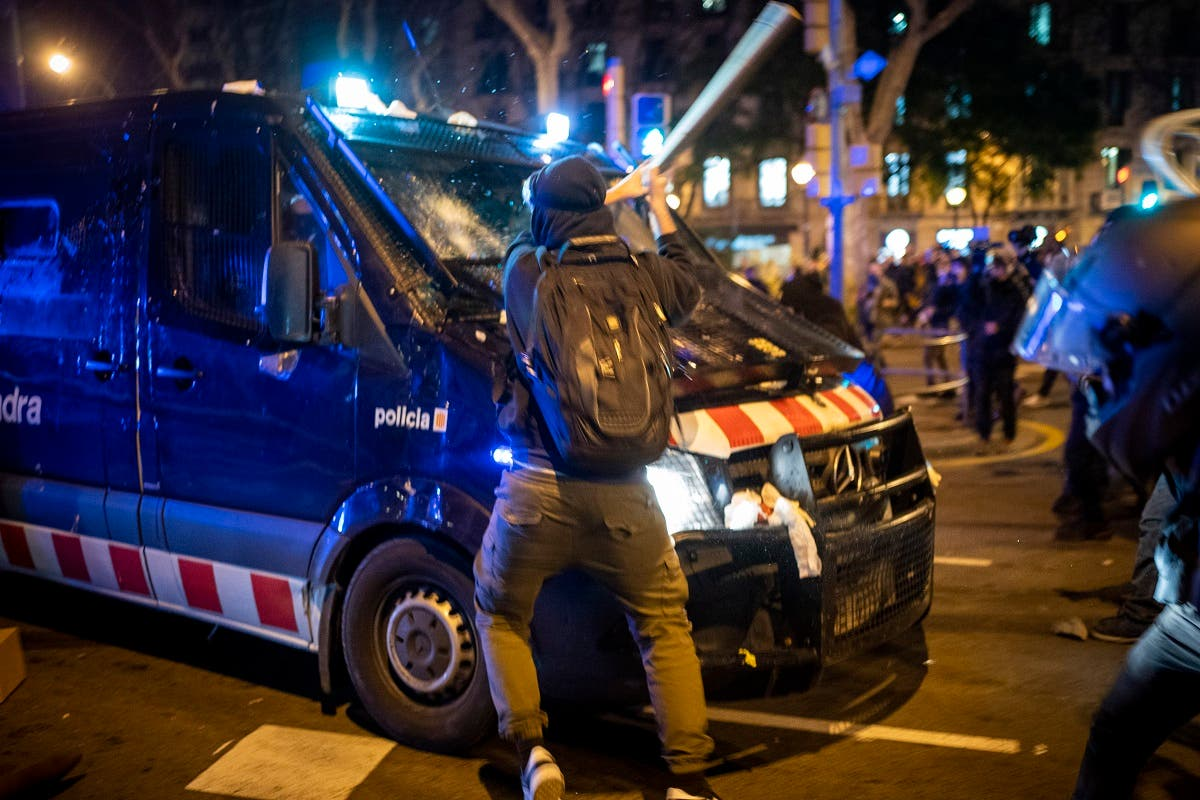 A demonstrator hits a police van with a bat during clashes following a protest condemning the arrest of rap singer Pablo Hasél in Barcelona, Spain, on February 17, 2021. (AP)
