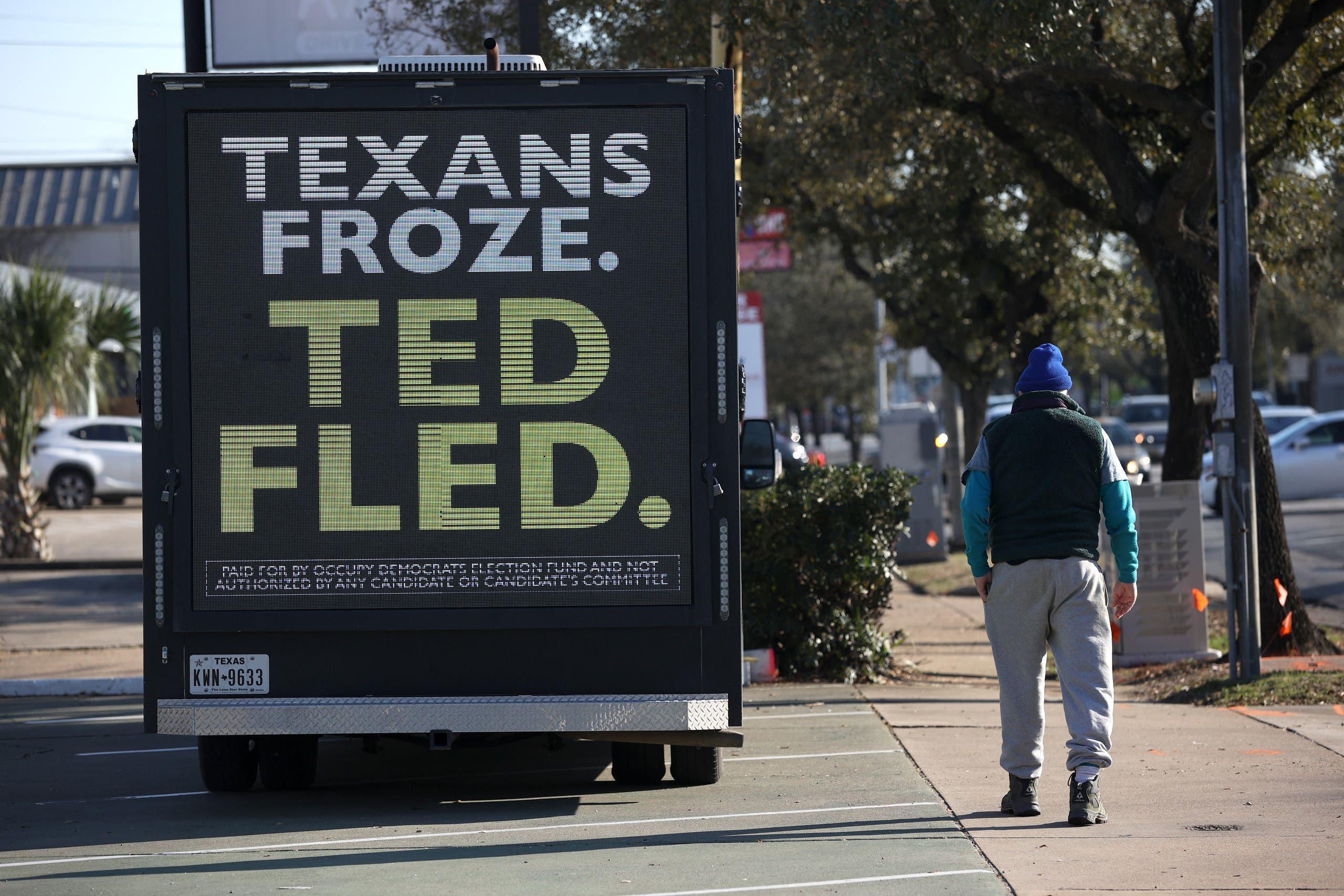لافتة تنتقد السيناتور تيد كروز حيث كتب أهل تكساس يتجمدون وتيد يسافر (فرانس برس)