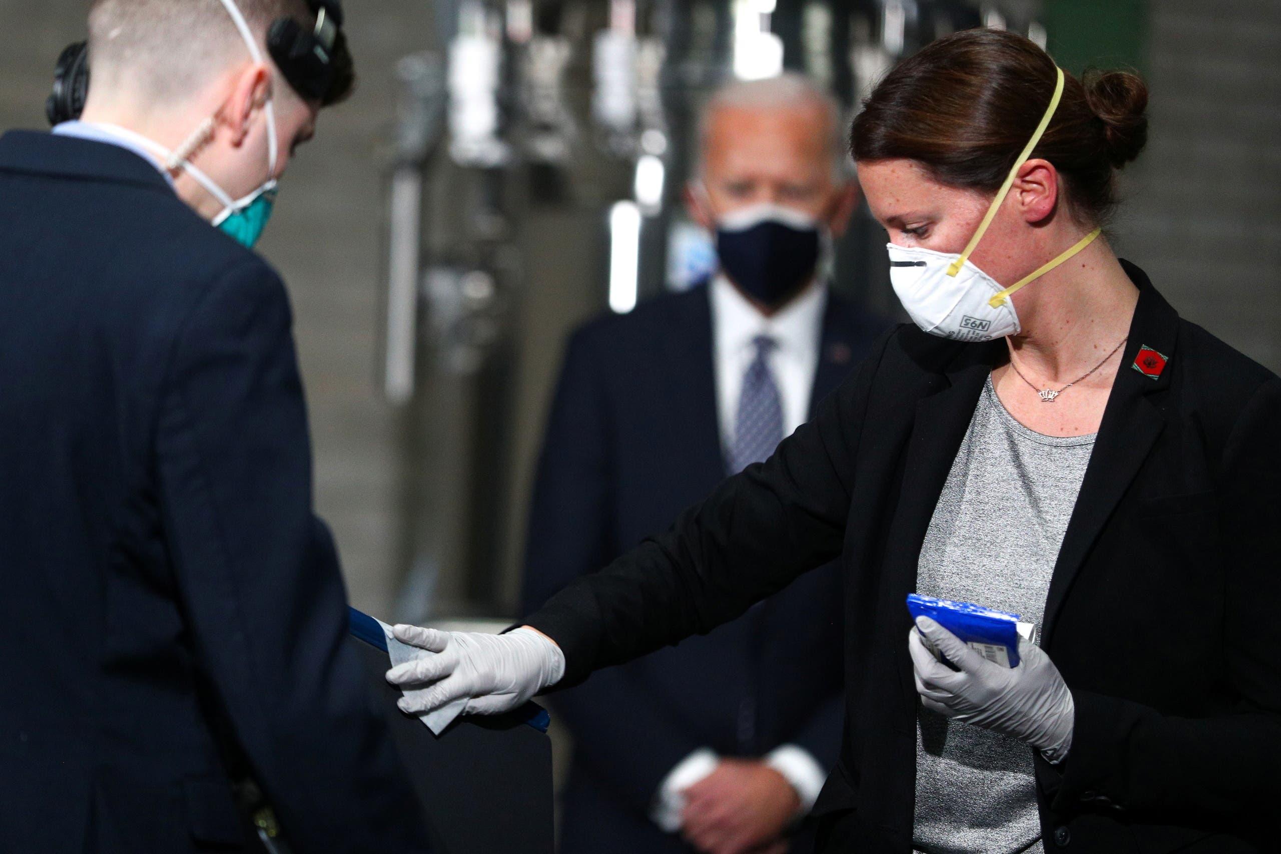 Staff members sanitize a podium space before U.S. President Joe Biden delivers remarks at a Pfizer manufacturing plant producing the coronavirus disease (COVID-19) vaccine in Kalamazoo, Michigan, U.S., February 19, 2021. (Reuters)