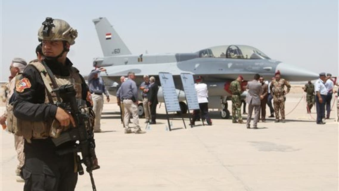 A member of the Iraqi SWAT team stands as security forces and others gather next to a US F-16 fighter jets at Balad air base, Iraq. (File photo: AP)