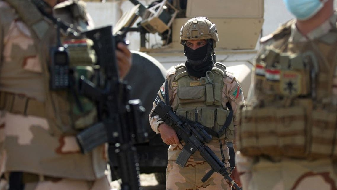 A member of the Iraqi force stands at attention during a search of the area in Tarmiyah, 35 kilometres (20 miles) north of Baghdad on February 20, 2021, following clashes with ISIS group fighters. (AFP)