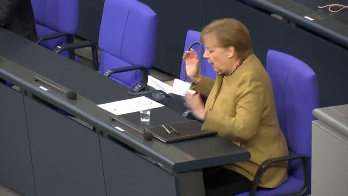 Angela Merkel panics after forgetting mask on lectern following speech. (Reuters)