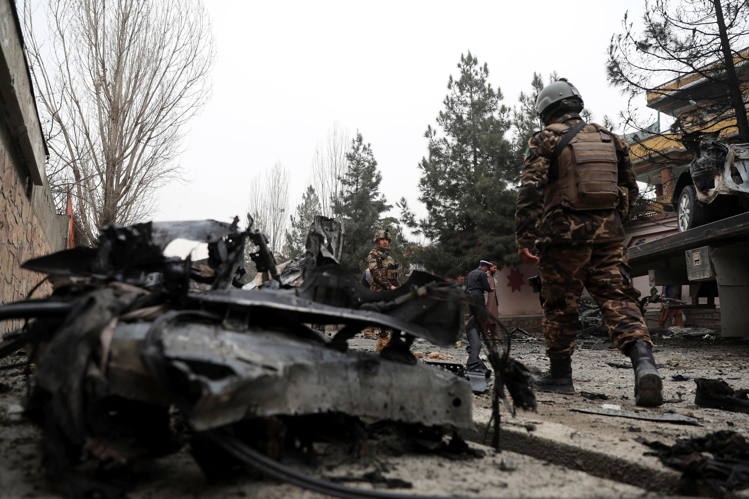 Security personnel inspect the site of a bomb attack in Kabul, Afghanistan, Saturday, Feb. 20, 2021.