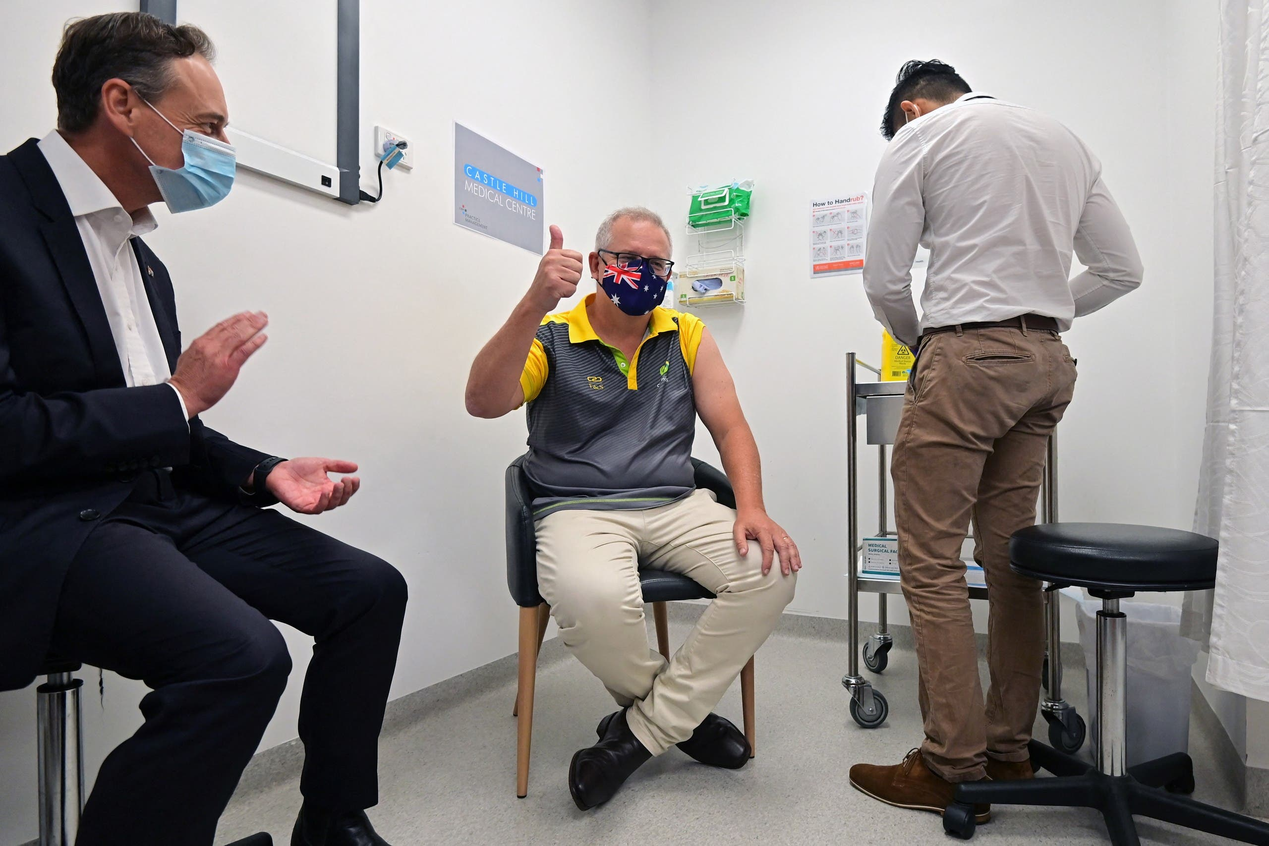 Australia's Prime Minister Scott Morrison reacts after receiving a dose of the Pfizer/BioNTech Covid-19 vaccine, as Minister for Health Greg Hunt (L) looks on, at the Castle Hill Medical Centre in Sydney on February 21, 2021.