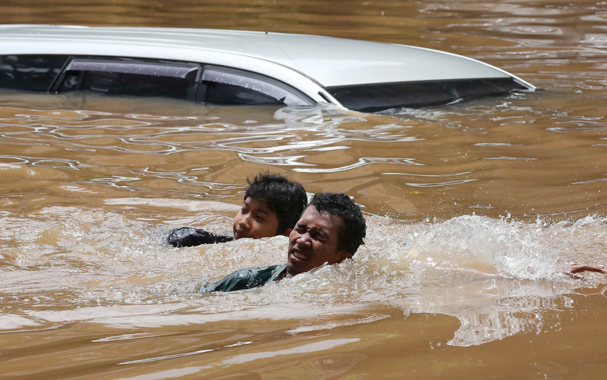 People swim through a flooded neighborhood following heavy rains in Jakarta, Indonesia, Saturday, February 20, 2021. (AP)