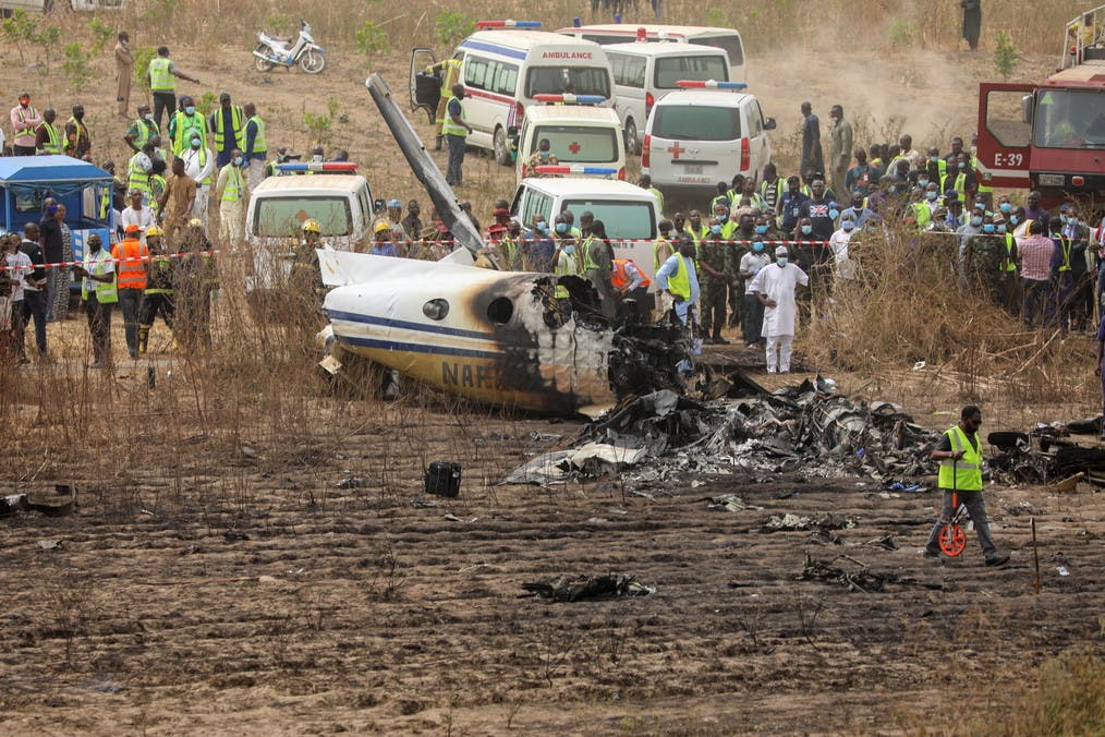 Rescuers and onlookers gather near the debris from a Nigerian air force plane, which according to the aviation minister crashed while approaching the Abuja airport runway, in Abuja, Nigeria February 21, 2021. (Reuters)