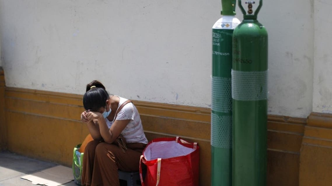 Relatives of COVID-19 victims queue to refill oxygen tanks, in Lima on February 9, 2021. (AFP)