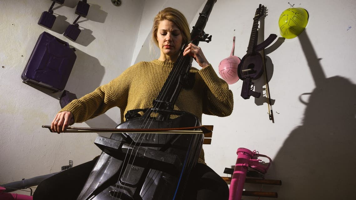 Cellist Milica Svirac plays a cello converted from a bazooka and army gas bucket, made by Serbian sculptor Nikola Macura at his studio, in Novi Sad on February 1, 2021. Macura, 42, is trying to transform these former forces of destruction into vessels of creation in a region that still bears the scars from the 1990s wars that unravelled Yugoslavia