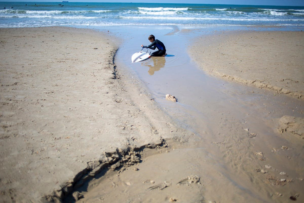 A surfer cleans his tar covered surfboard from an oil spill in the Mediterranean Sea in Gador nature reserve near Hadera, Israel, Saturday, Feb. 20, 2021. (File photo: AP)