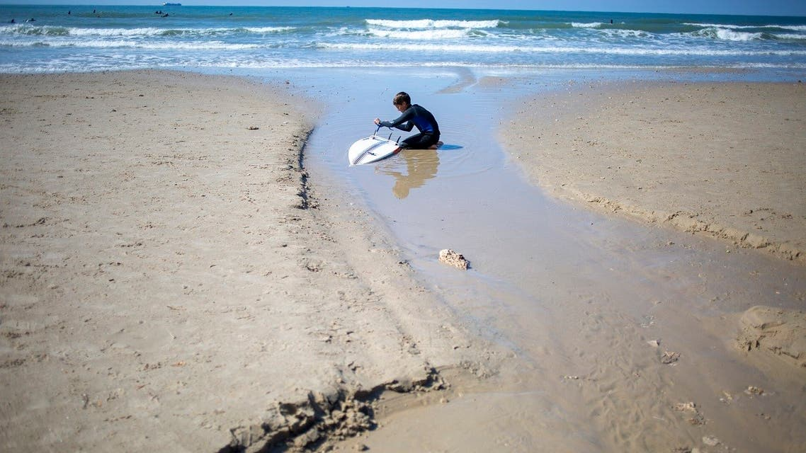 A surfer cleans his tar covered surfboard from an oil spill in the Mediterranean Sea in Gador nature reserve near Hadera, Israel, Saturday, Feb. 20, 2021. (AP/Ariel Schalit)