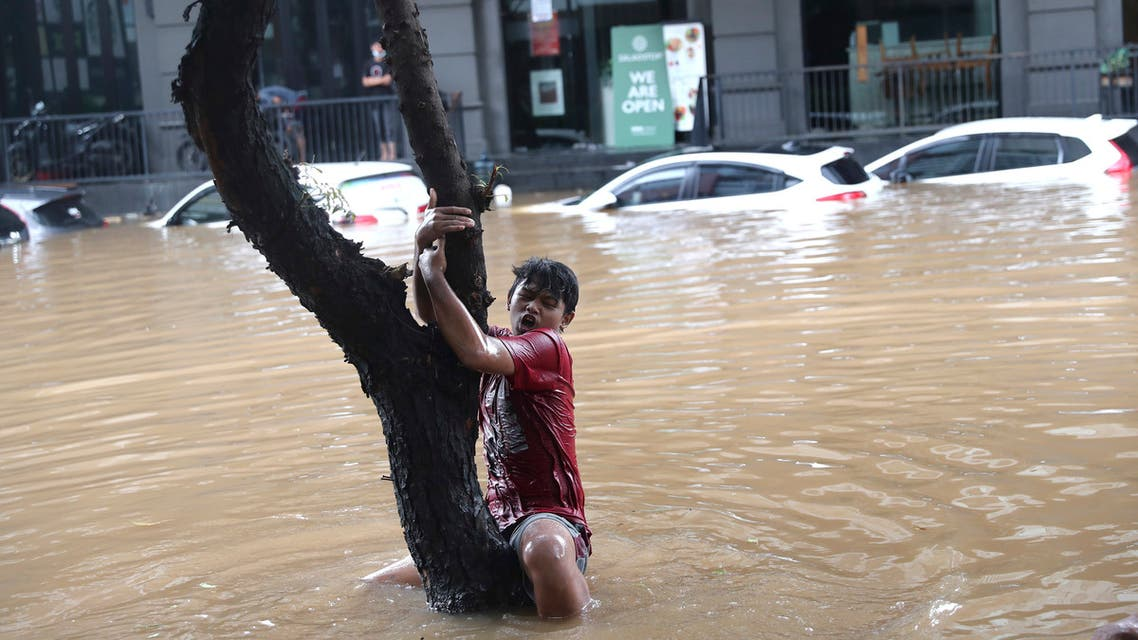 A man grabs a tree to keep from being swept away by flood water through a flooded neighborhood following heavy rains in Jakarta, Indonesia, Saturday, February 20, 2021. (AP)