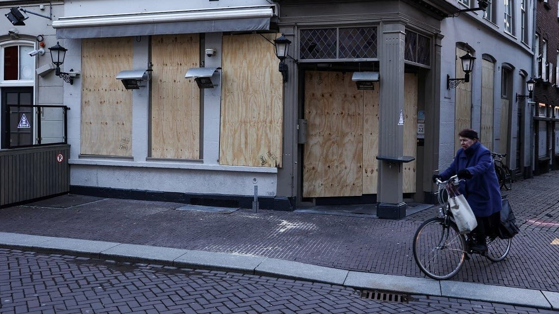 A woman cycles her bike past a board-covered closed shop in Den Bosch, on January 26, 2021 a day, after police clashed with groups of demonstrators protesting against the introduction of a coronavirus curfew over the weekend. (Kenzo Tribouillard/AFP)