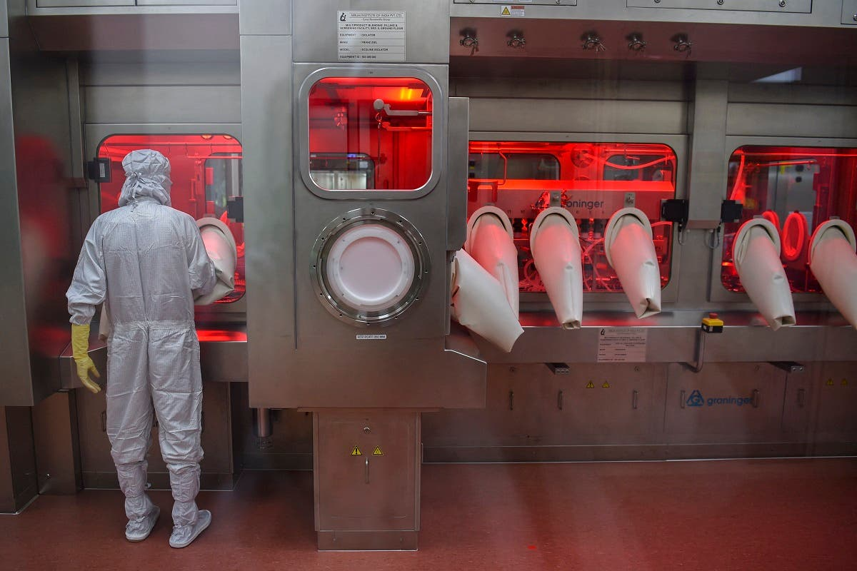 In this file photo taken on January 22, 2021, an employee in protective gear works on an assembly line for manufacturing vials of coronavirus vaccine at India's Serum Institute in Pune. (Punit Paranjpe/AFP)