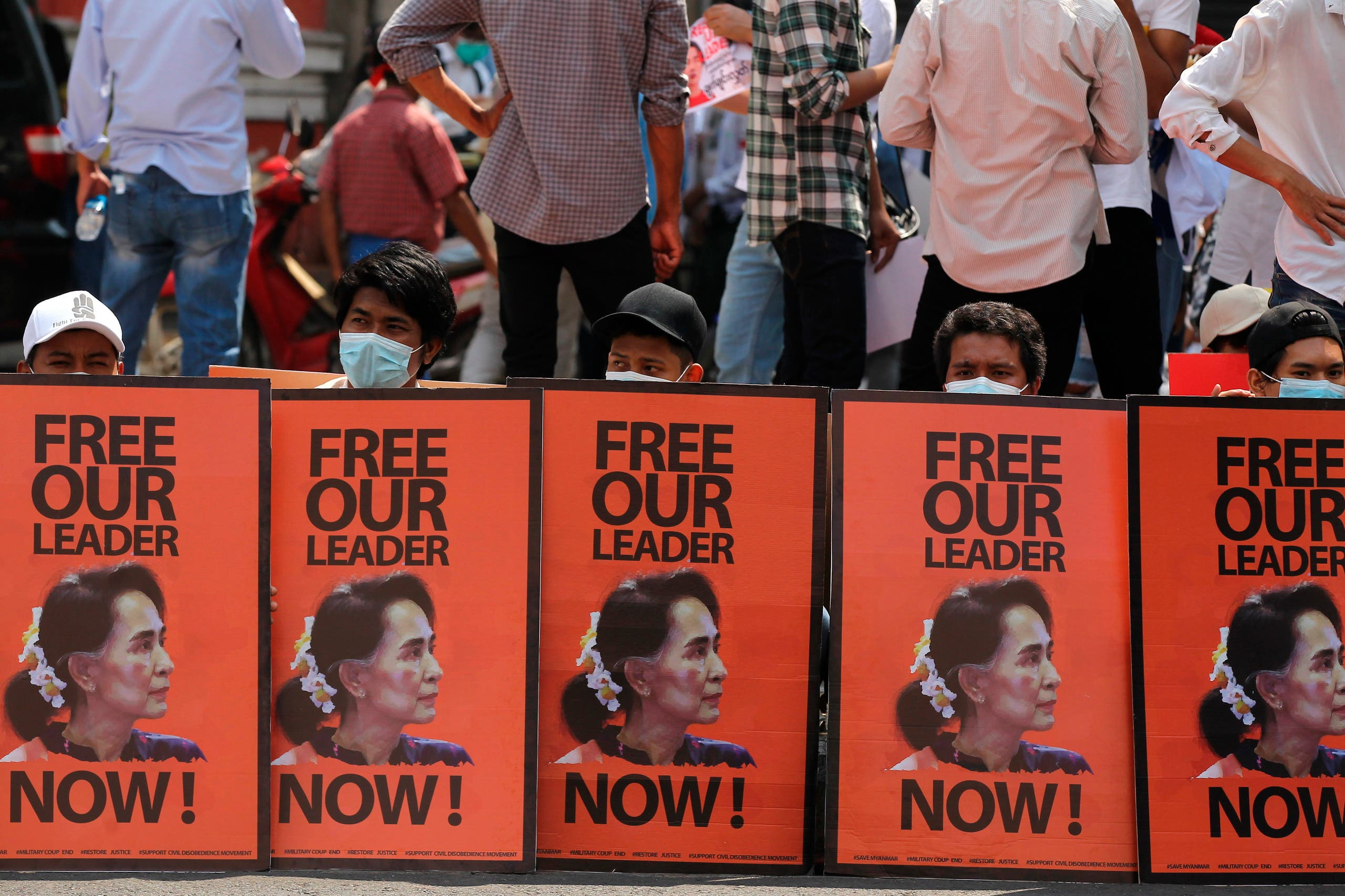Anti-coup protesters sit behind posters with an image of deposed Myanmar leader Aung San Suu Kyi during a rally in Yangon, Myanmar, Monday, Feb. 22, 2021. (AP)