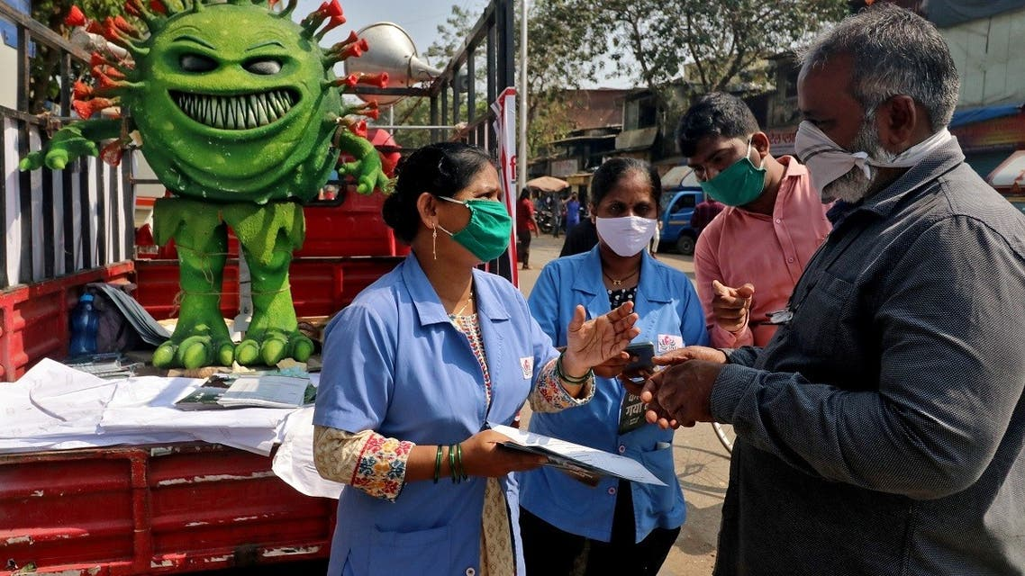 Volunteers distribute pamphlets during an awareness campaign on the spread of the coronavirus disease (COVID-19) on a street in Mumbai, India, on February 22, 2021. (Reuters)