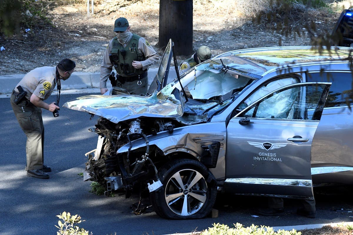 Los Angeles County Sheriff's Deputies inspect the vehicle of golfer Tiger Woods, who was rushed to hospital after suffering multiple injuries, after it was involved in a single-vehicle accident in Los Angeles, California, US, on February 23, 2021. (Reuters)