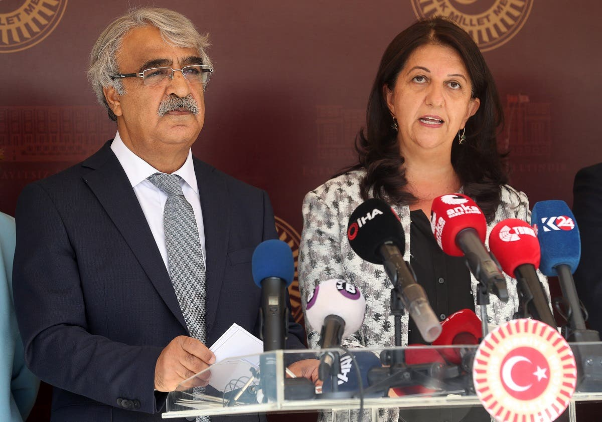 Co-chairmans of the pro-Kurdish Peoples' Democratic Party (HDP) Pervin Buldan (R) and Mithat Sancar (L) hold a press conference following the arrest of 82 people, including members of their party, outside the Parliament building, Ankara, October 1, 2020. (Adem Altan/AFP)