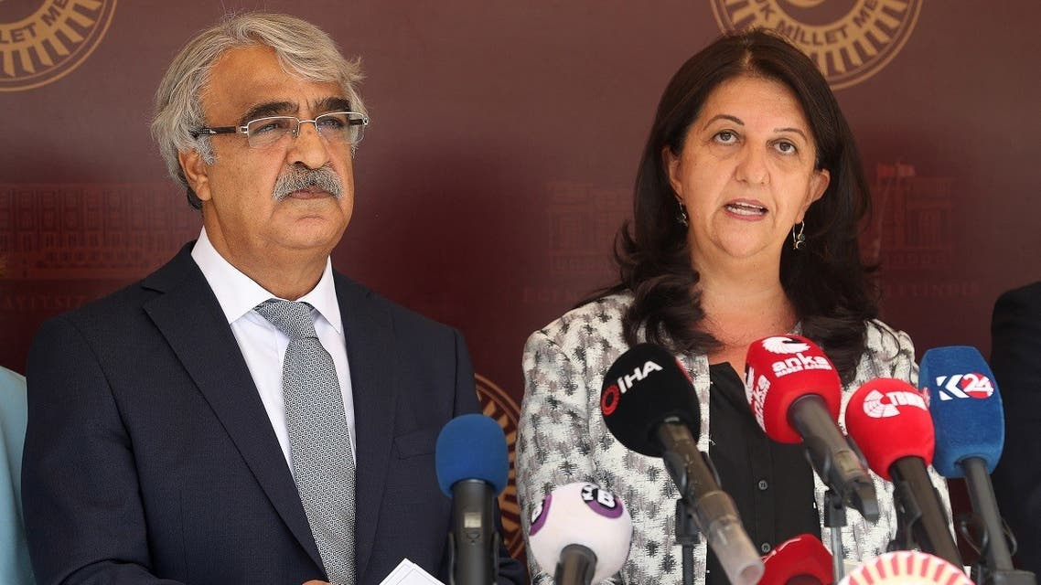 Co-chairmans of the pro-Kurdish Peoples' Democratic Party (HDP) Pervin Buldan (R) and Mithat Sancar (L) hold a press conference with their members as they boycott the first sessiom of the Grand National Assembly's 27th term following the arrest of 82 people, including members of their party, outside the Parliament building in Ankara on October 1, 2020. (Adem Altan/AFP)