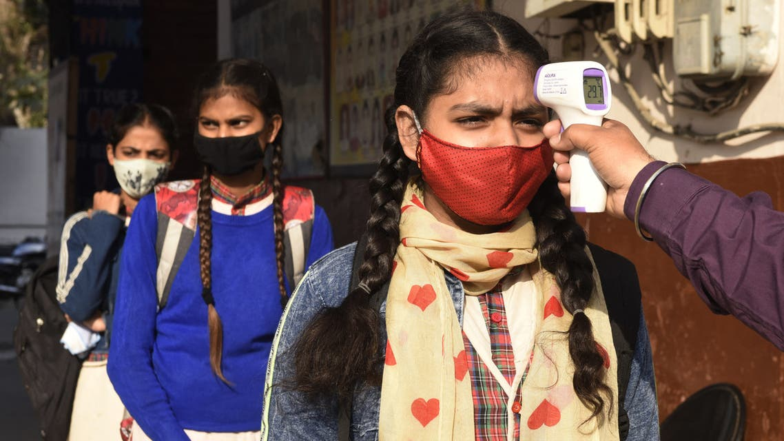 A school worker checks the body temperature of student as they arrive at a government girls school amid the ongoing COVID-19 coronavirus disease pandemic, in Amritsar on February 24, 2021. (File photo: AFP)