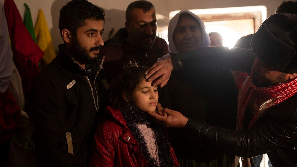 In this Feb. 12, 2020 photo, Malak Saad Dakhel, 11, is anointed by a holy man inside a Yazidi shrine as she is welcomed home by her relatives after her escape from Syria, in Sharia, Iraq. She was captured by ISIS militants in 2014 and was recently found at al-Hol camp living with a Syrian family. (AP)