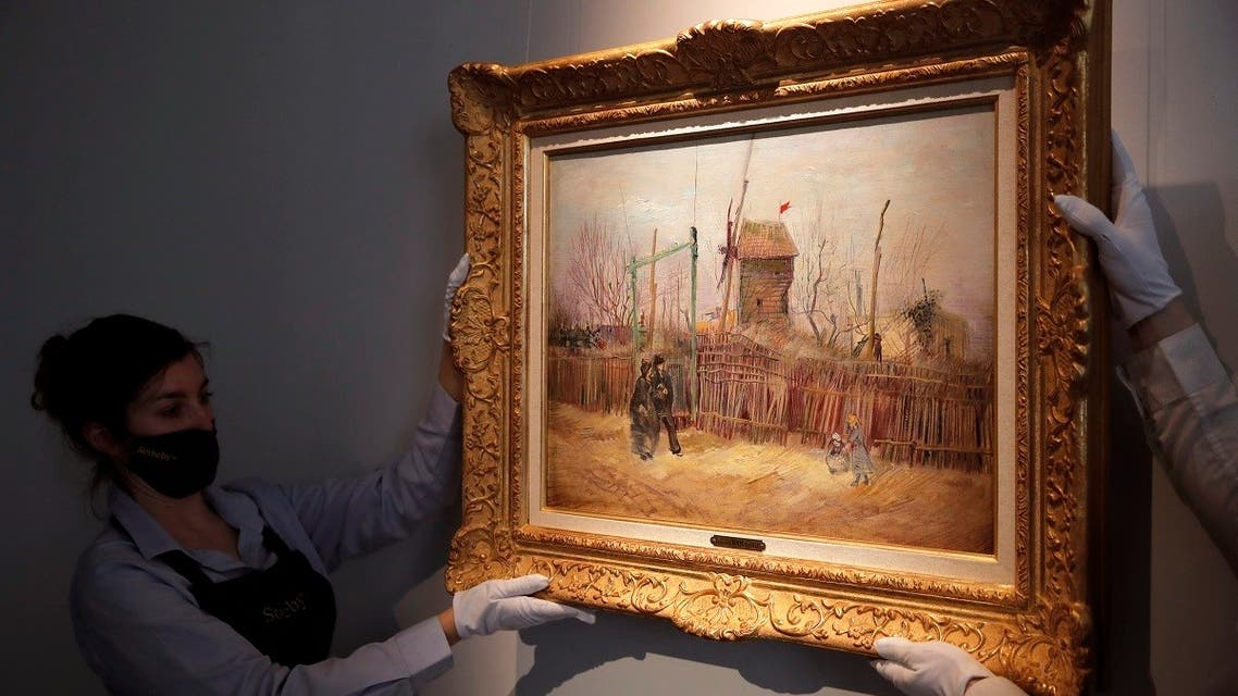 Sotheby's personnel display 'Scene de rue à Montmartre' (Street scene in Montmartre), a painting by Dutch master Vincent van Gogh at Sotheby's auction house in Paris, on February 25, 2021. (AP)