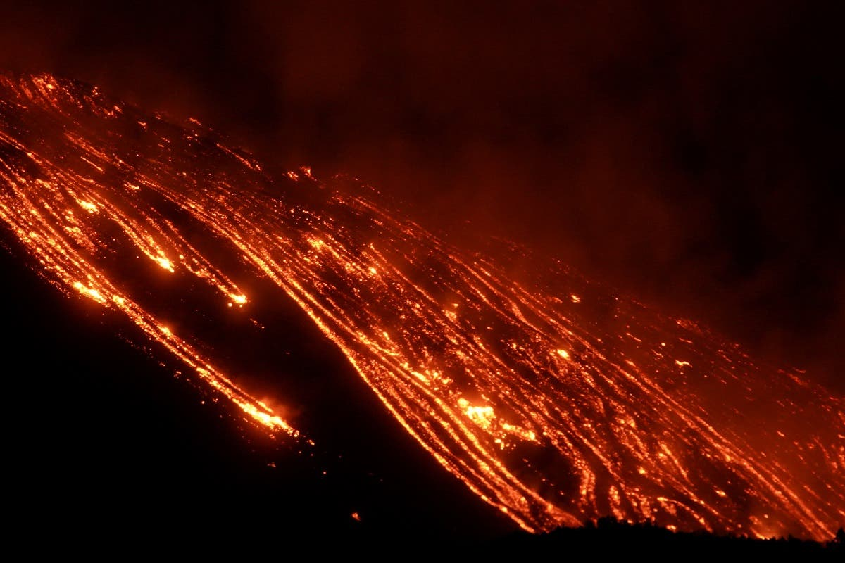 Streams of red hot lava flow as Mount Etna, Europe's most active volcano, continues to erupt, seen from Zafferana Etnea, Italy, on February 21, 2021. (Reuters)
