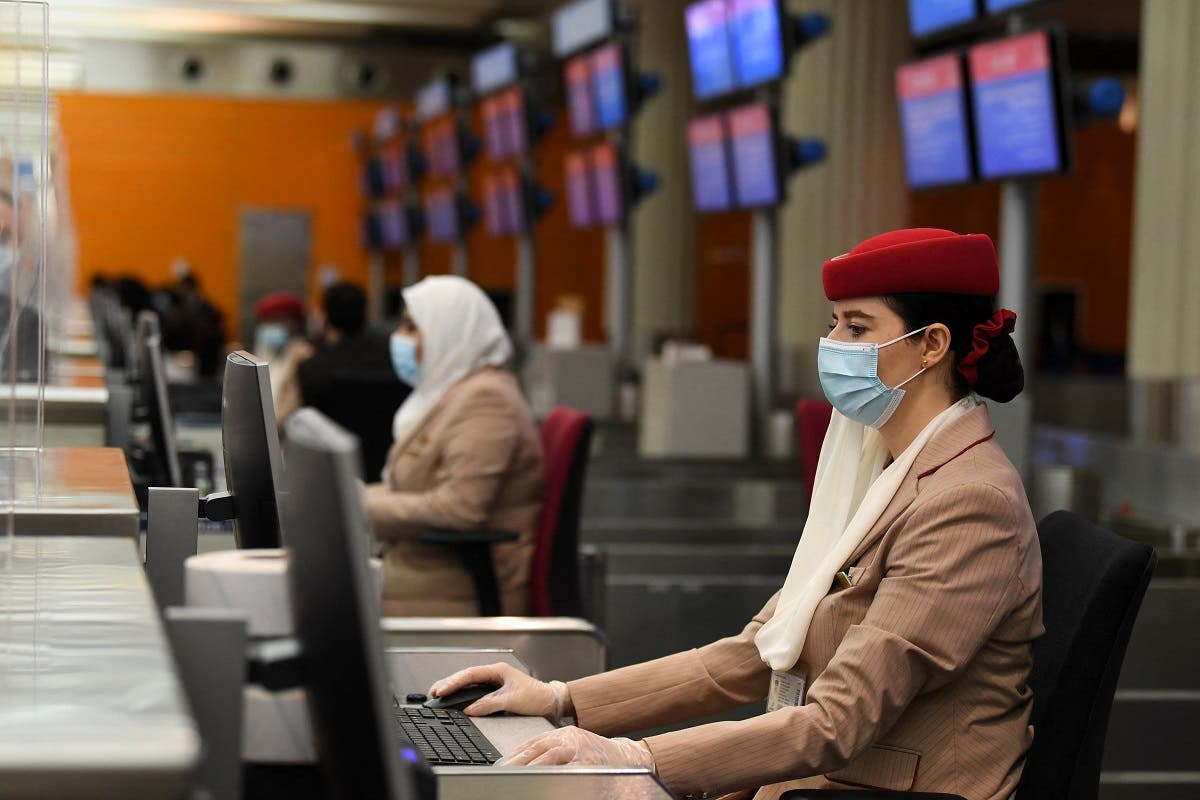Ground hostesses of the Emirates airlines wear face masks and assist travellers fromp behind glass windows at Dubai International Airport on May 22, 2020, after the resumption of scheduled operations by the Emirati carrier, amid the ongoing novel coronavirus pandemic crisis. (AFP)