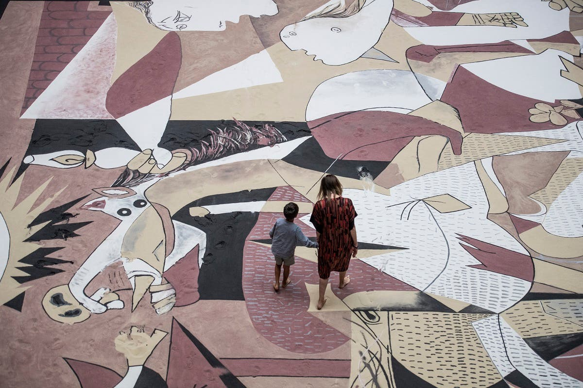 A mother and child walk on a giant reproduction in sand of Spanish artist Pablo Picasso's Guernica painting, during Taiwanese-American artist Lee Mingwei's performance Guernica in Sand part of his Gifts and Rituals exhibition at the Martin-Gropius-Bau museum in Berlin on July 4, 2020.  (AFP)