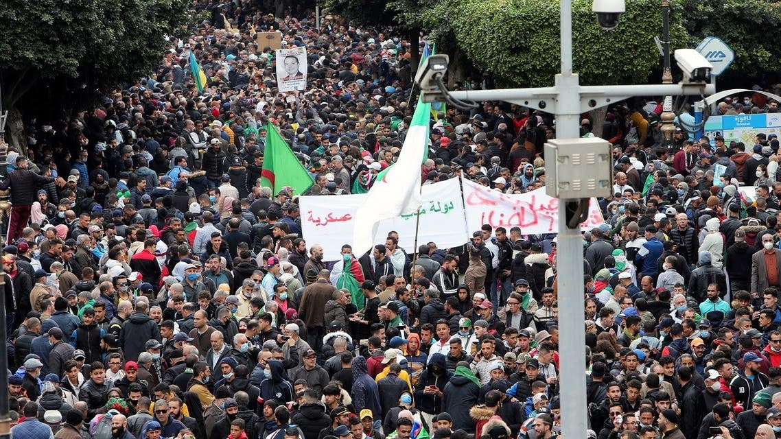 Demonstrators carry banners and flags as they march to mark the second anniversary of a mass protest movement demanding political change, in Algiers, Algeria February 22, 2021. (Reuters)